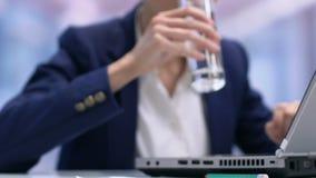 Capo vendite di signora che lavora al computer portatile ed all'acqua potabile, equilibrio liquido nel corpo video d archivio