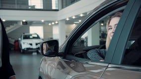 Capo vendite Gives il cliente le chiavi dall'automobile video d archivio