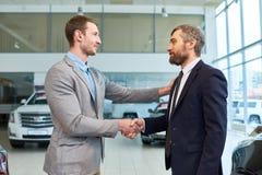 Capo vendite Shaking Hands con l'automobile d'acquisto del cliente immagine stock libera da diritti