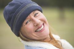 Capo y chaqueta calientes sonrientes alegres de la mujer imagen de archivo libre de regalías