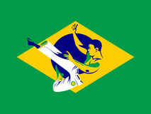 Capoeira fighter. Jumping over Brazil flag Stock Photos