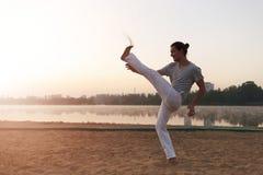 Capoeira sulla spiaggia, vicino al lago nell'esecutore del parco uno, alla s Fotografia Stock Libera da Diritti
