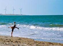 Capoeira Training on the beach in Brazil. A man doing capoeira on the beach of Icarai in Brazil with windmills in the background Stock Photo