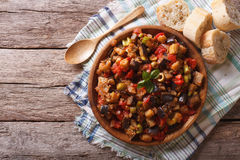 Caponata with aubergines in a wooden plate. Horizontal top view Royalty Free Stock Photos
