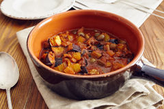 Caponata. Eggplant caponata, traditional sicilian dish. Served in a classic ceramic pan over a napkin on an aged wooden table. Surrounded by a silver spoon and a Royalty Free Stock Image