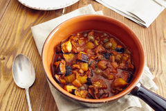 Caponata. Eggplant caponata, traditional sicilian dish. Served in a classic ceramic pan over a napkin on an aged wooden table. Surrounded by a silver spoon and a Stock Image