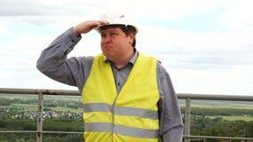 Caporeparto, ingegnere, lavoratore o architetto maschio del costruttore sull'uomo del cantiere della costruzione che sembra dista video d archivio