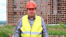 Caporeparto, lavoratore o architetto maschio del costruttore lavoranti alla condizione del cantiere della costruzione mentre guar video d archivio