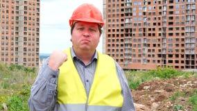 Caporeparto, lavoratore o architetto maschio del costruttore sul cantiere della costruzione che minaccia il suo pugno archivi video