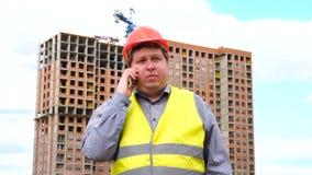 Caporeparto, lavoratore o architetto maschio del costruttore sul cantiere della costruzione parlanti dal suo telefono archivi video