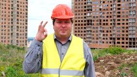 Caporeparto, lavoratore o architetto maschio del costruttore sul gesto di approvazione di rappresentazione del cantiere della cos archivi video