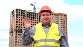 Caporeparto, lavoratore o architetto maschio del costruttore sul saluto del cantiere della costruzione ondeggiando la sua mano video d archivio