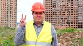Caporeparto, lavoratore o architetto maschio del costruttore sul segno di vittoria di rappresentazione del cantiere della costruz stock footage