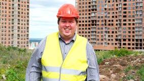 Caporeparto, lavoratore o architetto maschio del costruttore sulla condizione del cantiere della costruzione mentre ridendo e sor video d archivio