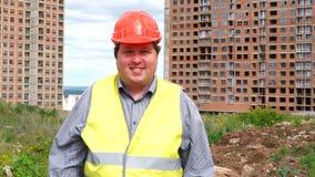 Caporeparto o architetto maschio del costruttore che lavora alla condizione del cantiere della costruzione mentre ridendo e sorri video d archivio