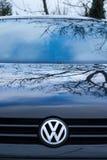 Capot d'une voiture noire avec un emblème argenté de Volkswagen Le capot reflète l'arbre et le ciel image libre de droits