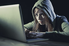 Capot de port de jeune femme de l'adolescence attirante sur entailler le concept de crime de cyber de cybercriminalité d'ordinate Photo stock