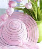 Capot et tulipes roses dans le vase Image stock