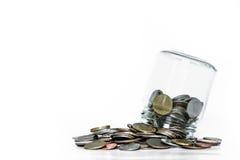 Capovolga il barattolo di vetro con le monete rovesciate fuori, su fondo bianco Fotografia Stock