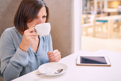 Cappaccino sorvendo da mulher em um café brilhante com tabuleta Foto de Stock