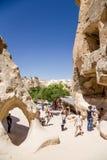 Cappadocia,土耳其 游人参观雕刻了入在修士的细胞Pashabag (修士谷)的谷的岩石 免版税库存照片