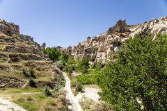 Cappadocia,土耳其 :一个山谷的风景看法与洞的到岩石里在Goreme国家公园  库存照片