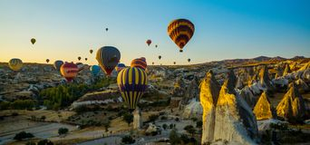 Cappadocia, Goreme, Anatolia, Turkey: Scenic vibrant view of balloons flight in Cappadocia valley in sunrise rays. Beautiful dawn in the valleys. Favorite stock images