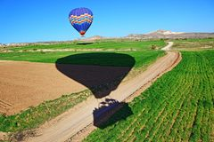 Hot air balloons ride in spring landscape Turkey. Landing hot air balloons in green fields over dirt path in Cappadocia/Kapadokia Turkey.Cappadocia has unreal Royalty Free Stock Images