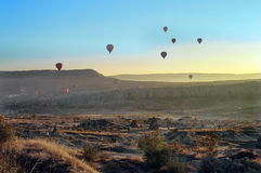 Hilly landscape and balloon at sunset. Balloons. Goreme, Cappadocia - Landmark attraction in Turkey Stock Photography