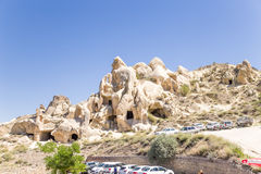 Cappadocia, Turkey. Car parking on the background of cliffs with caves in Goreme National Park Stock Photos