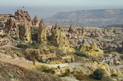 Hilly landscape. Balloons. Goreme, Cappadocia - landmark attraction in Turkey. Hilly landscape. Balloons. Volcanic formations converted into dwelling - Goreme Royalty Free Stock Photography