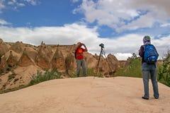 Cappadocia, Turkije - April 29, 2014: De Rode Vallei van steenkolommen De toeristen worden gefotografeerd op een achtergrond van  Royalty-vrije Stock Afbeeldingen