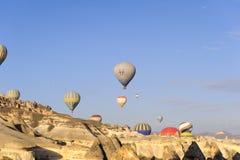 CAPPADOCIA, TURQUIA - ABRIL, 08, 2017: Muitos balões sobre as formações de rochas extraordinárias balançam montes do vale do cogu Imagens de Stock Royalty Free