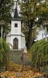 Cappella bianca fra le latifoglie con le foglie colorate Immagini Stock Libere da Diritti