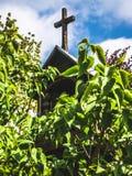 Cappella di legno nascosta nelle foglie di un albero immagini stock