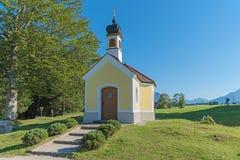 Cappella di pellegrinaggio e banco nelle alpi bavaresi, landsca di estate Fotografia Stock