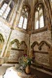 Cappella medievale con i fiori sull'altare di pietra Fotografie Stock Libere da Diritti