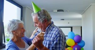 Cappelli d'uso del partito delle coppie senior che ballano alla festa di compleanno 4k stock footage