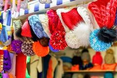 Cappelli del pom di Pom che appendono per la vendita al mercato di Natale di Riga Immagini Stock