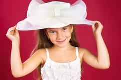 Cappello bianco adattantesi sorridente della ragazza che propone nello studio Immagini Stock