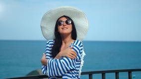 Cappello bianco d'uso ed occhiali da sole di viaggio della donna allegra di modo che posano al fondo del mare di orizzonte stock footage