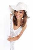 Cappello bianco da portare della donna che tiene scheda in bianco. Fotografia Stock