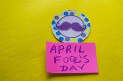 Cappello a cilindro di carta con i baffi dipinti ed il giorno del ` s del pesce d'aprile di parole, fondo giallo Fotografie Stock Libere da Diritti