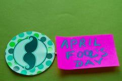 Cappello a cilindro di carta con i baffi dipinti ed il giorno del ` s del pesce d'aprile di parole, fondo verde Fotografia Stock Libera da Diritti