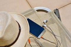 Cappello con un telefono cellulare e le cuffie su una sedia di vimini fotografie stock libere da diritti