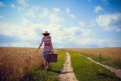 Cappello d'uso della donna con la valigia sulla strada in grano Fotografia Stock