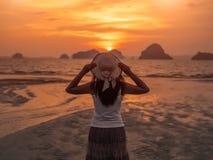 Cappello d'uso di estate della giovane donna del primo piano nell'ambito dell'alba Fotografie Stock