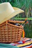 Cappello da cowboy, attrezzatura di pesca, asciugamani e canestro di vimini, natura Immagine Stock Libera da Diritti
