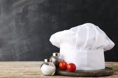 Cappello del cuoco unico con sale, pepe ed il pomodoro fotografia stock