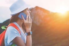 Cappello della donna allegra di avventura e zaino d'uso che parlano sul telefono cellulare, riserva dell'alta montagna al tramont Immagini Stock
